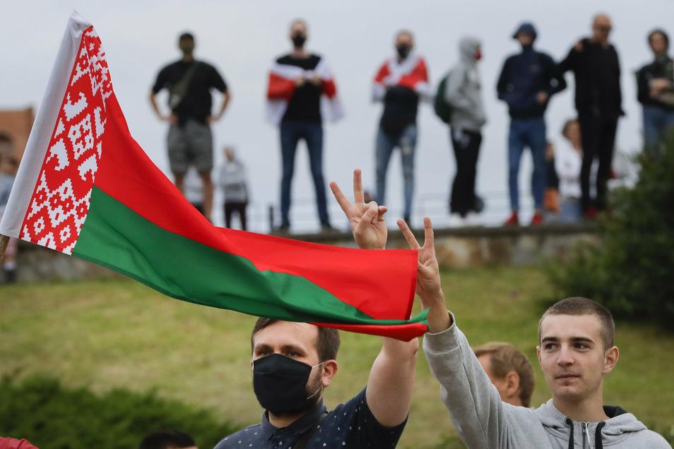 Männer mit belarussischer Nationalflagge protestieren auf einer Straße gegen die Wahlergebnisse.