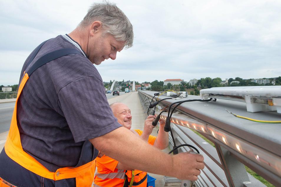 René Kupke (l.) und Thomas Müller wechselten in dieser Woche mehrere ausgefallene LED-Lichtleisten auf der Waldschlößchenbrücke.