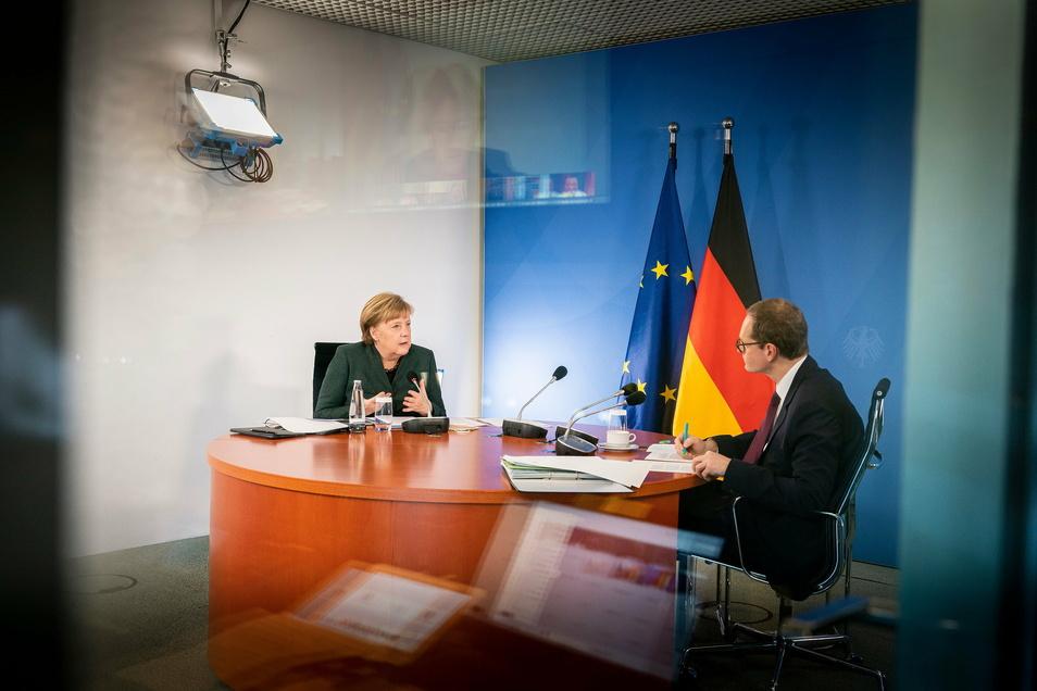 Bundeskanzlerin Angela Merkel (CDU) und Michael Müller, Regierender Bürgermeister von Berlin, sitzen im Bundeskanzleramt gemeinsam bei der Videokonferenz mit den Ministerpräsidentinnen und Ministerpräsidenten der Länder zur Corona-Situation.