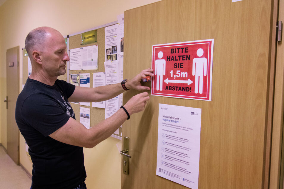 Schulleiter Jan Genscher von der Oberschule Waldheim beklebt die Türen der Schule mit Hinweisen zur Abstandregelung.