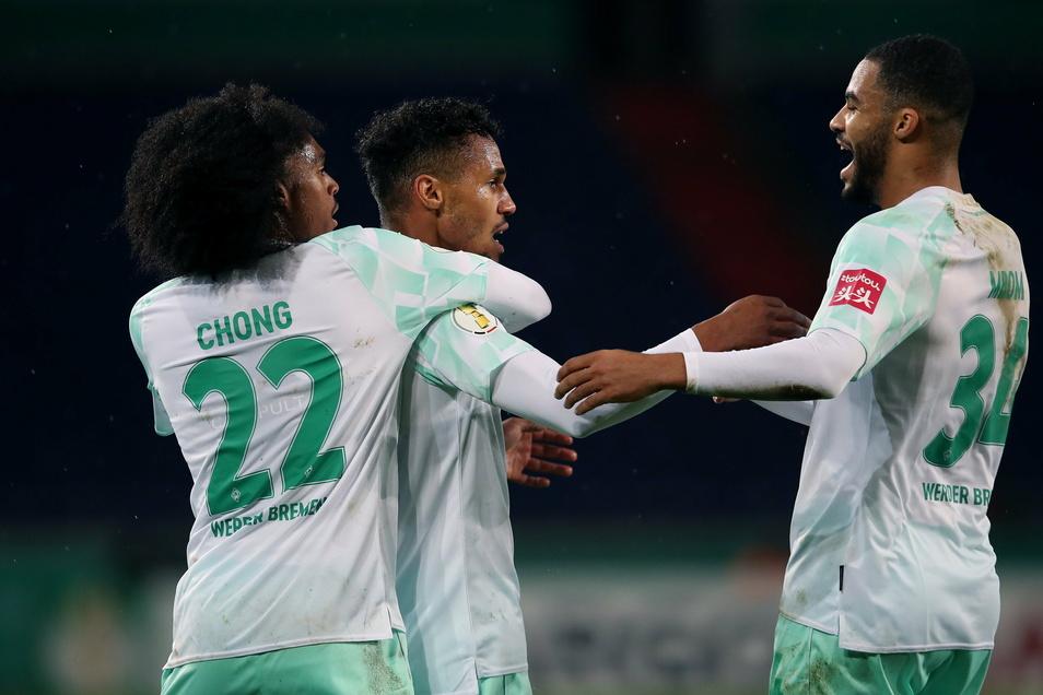 Der Bremer Theodor Gebre Selassie (M) jubelt nach seinem Treffer zur 1:0-Führung mit Tahith Chong (l) und Jean Manuel Mbom (r).