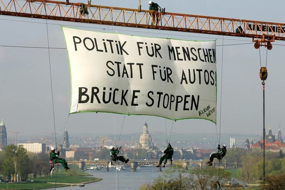 """Erneuter Protest im April 2008  Die Umweltaktivisten hingen ein Banner mit der Aufschrift """"Politik fuer Menschen statt fuer Autos, Brücke Stoppen"""" auf."""