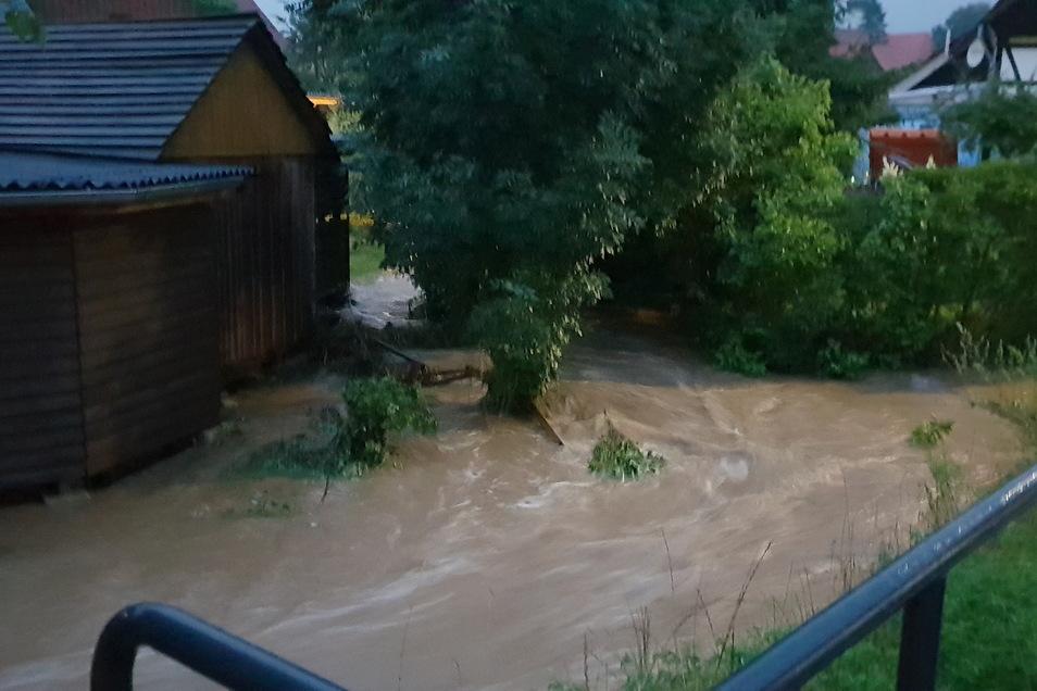 Der Eckartsbach in Oberseifersdorf überschwemmte hier ein Grundstück. Auch im Mittelherwigsdorfer Ortsteil musste die Feuerwehr Keller auspumpen und Sandsäcke verteilen.