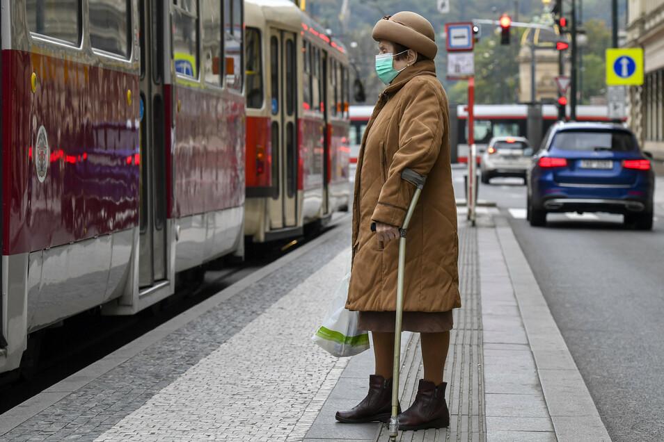 Eine Frau mit Mund-Nasen-Schutz wartet in Prag auf die Straßenbahn.