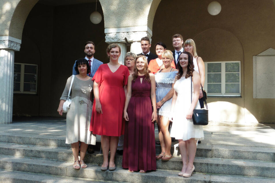 Liesbet Nicko (weinrotes Kleid) und Dominik Fietz (hinter Lisbet Nicko stehend) sind zwei der Absolventen, die nun weiter beschäftigt werden.