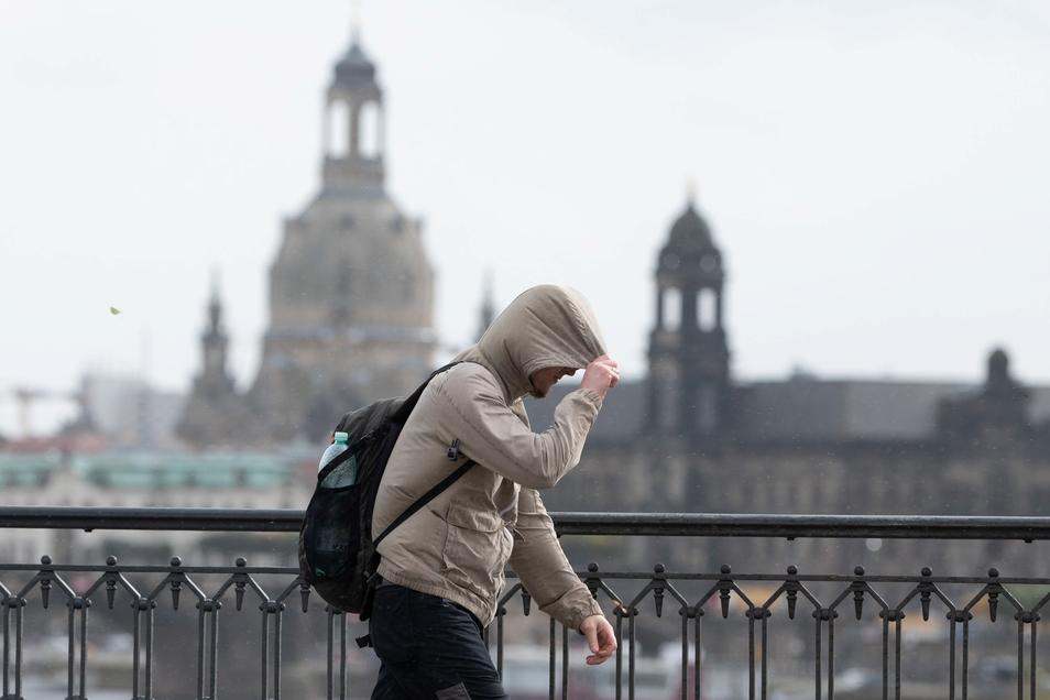 Ein Passant geht bei starkem Gegenwind vor der Kulisse der Frauenkirche über die Marienbrücke. Der Herbststurm hatte Sachsen am Donnerstag fest im Griff.
