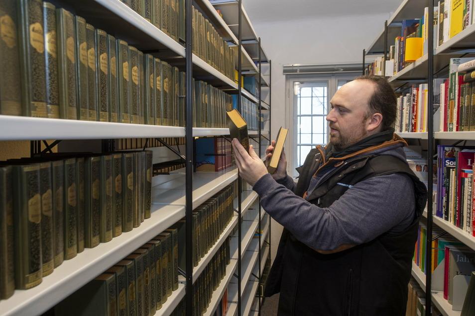 Robin Leipold, Wissenschaftlicher Museumsdirektor, stellt Bücher in die neue Forschungsbibliothek.
