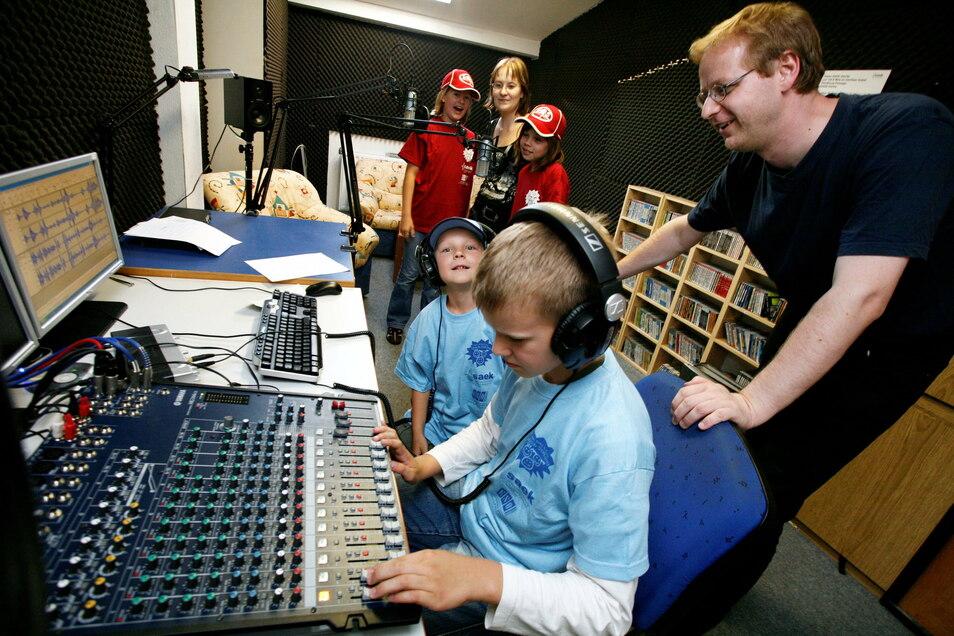 Studioleiter Olav Giewald (rechts) erklärt Kindern die Radiotechnik beim Ausbildungskanal SAEK. 2008 startete der Kanal mit neuen Medienprojekten für Schulen.