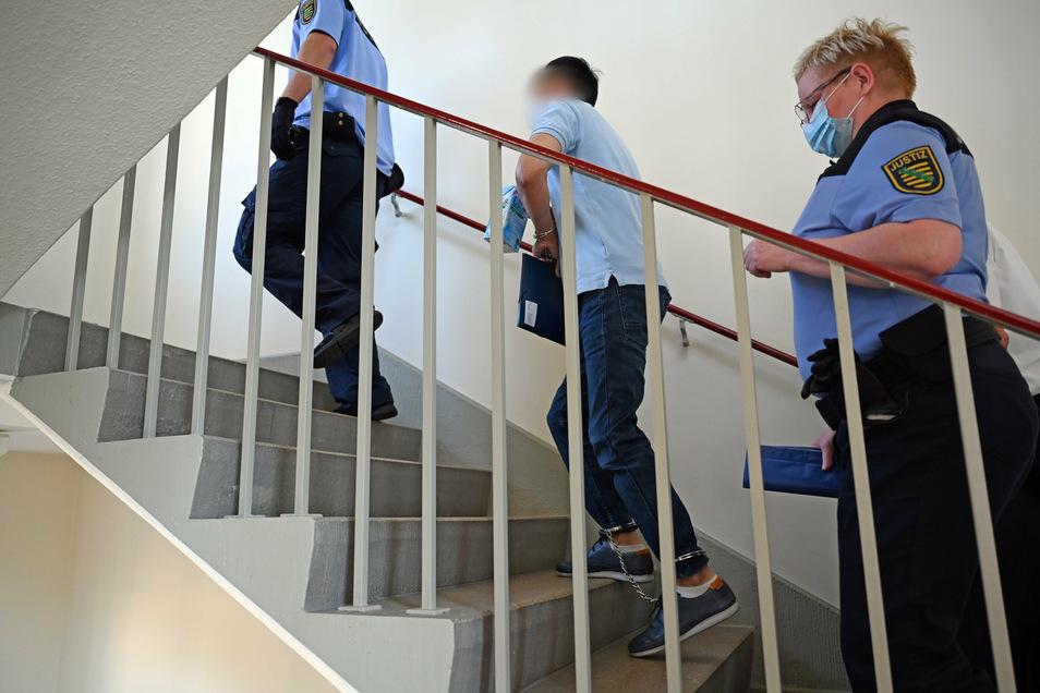 Ein wegen zweifachen Mordes angeklagter Mann (M) wird im Landgericht Chemnitz über eine Treppe von Justizbeamten zum Verhandlungssaal geführt.