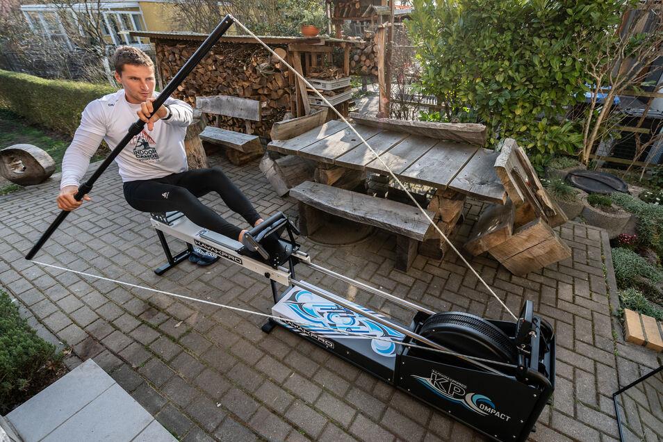 Dresdens Kanu-Olympiasieger Tom Liebscher trainiert in seinem Garten auf einem Paddelergometer. Nach der Olympia-Verschiebung auf kommendes Jahr hält er sich fit.