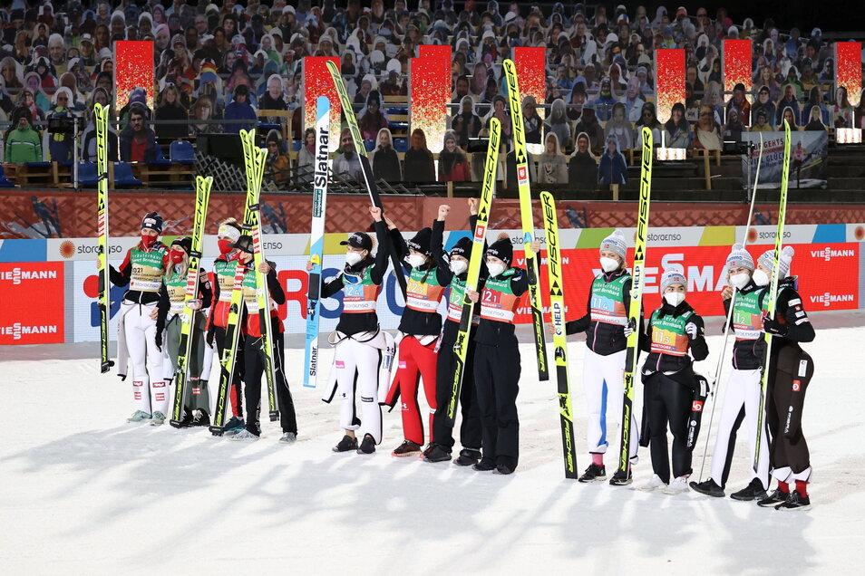 Skispringerinnen aus Österreich, Slowenien und Norwegen (l-r) stehen nach dem Wettkampf in Oberstdorf zusammen vor den Papp-Zuschauern.