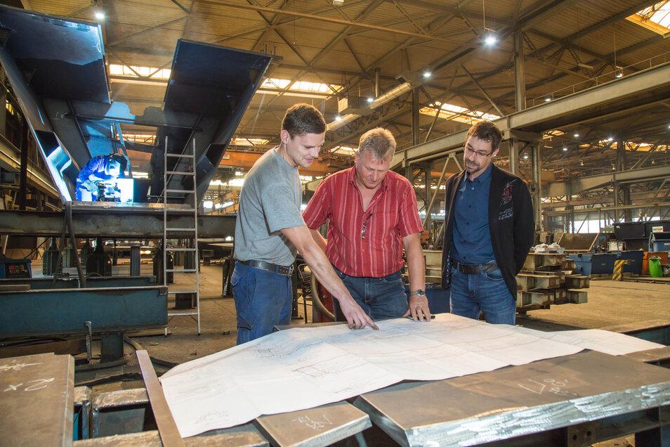 Geschäftsführer Robert Unger bespricht mit Fertigungsleiter Frank Sommer und Vorarbeiter Tobias Schubert (von rechts) die Pläne für ein Brückenbauwerk über die A 3 bei Regensburg.