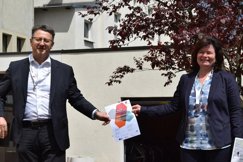 """Oberbürgermeisterin Beate Hoffmann und Bürgermeister Ralf Brehmer mit der Urkunde in der Hand, sowie das Logo """"Engagierte Stadt"""""""