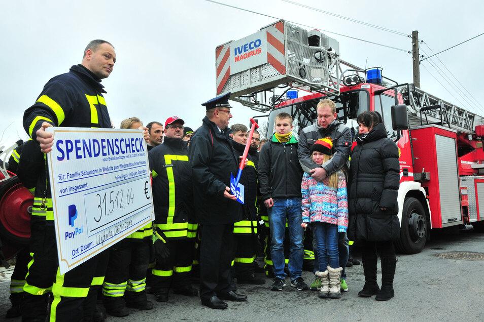 Ein halbes Jahr nach dem schlimmen Brand: Feuerwehrmann Mike Struck (l.) hält den Spendenscheck für die Weßnitzer Familie Schumann. Sie hatte am Heiligabend alles verloren, ihr Haus brannte komplett nieder. Struck organisierte spontan eine Spendensammlung