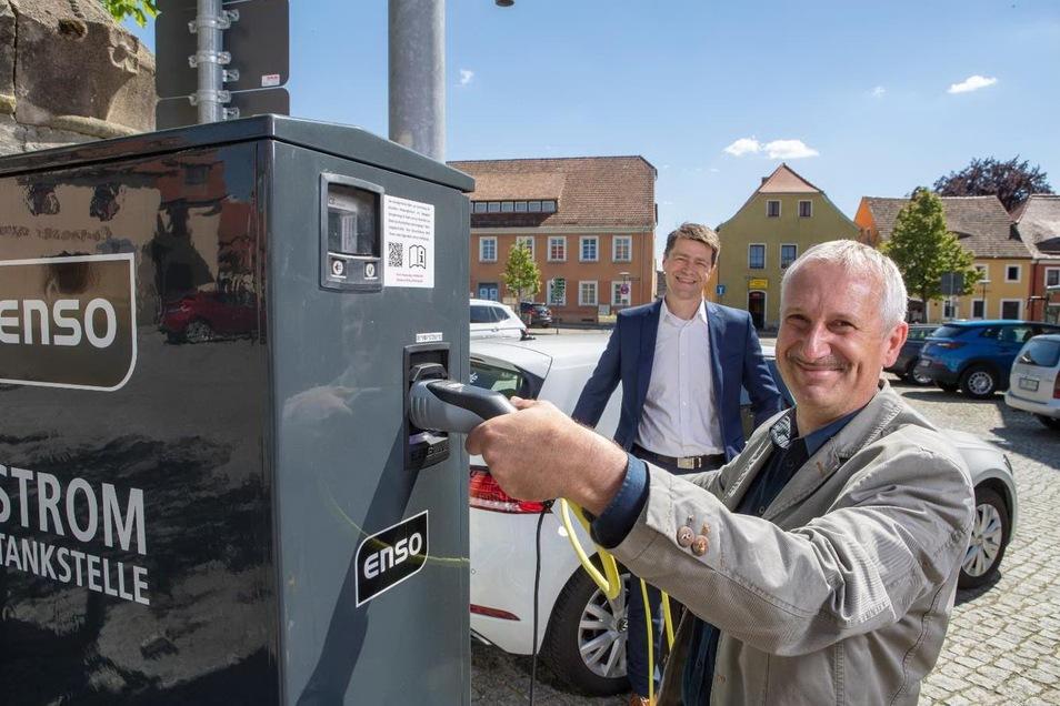 Auf dem Weißenberger Markt gibt es jetzt eine Ladesäule für Elektroautos. Bürgermeister Jürgen Arlt (vorn) hat sie zusammen mit Enso-Kommunalvertriebsleiter Gunnar Schneider in Betrieb genommen.