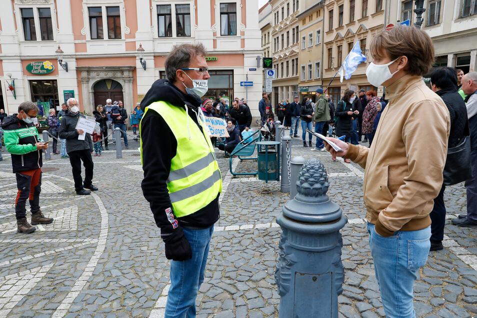 Mitorganisator Steffen Golembiewski (vorn links) hatte am Sonnabend bei der Veranstaltung der Kritiker der Corona-Maßnahmen auf der Neustadt in Zittau viele Fragen zu beantworten.
