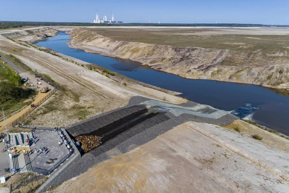 Das Einlaufbauwerk in den ehemaligen Braunkohletagebau Cottbus-Nord. Die gesamte Landmasse bis zu den Windrädern im Hintergrund soll später einmal von Wasser bedeckt sein.