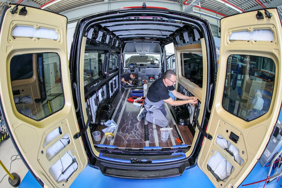 Zwei Mitarbeiter des MAN Bus Modification Centers (BMC) bauen eine Elektro-Kleinbus eTGE mit einer besonderen Innenverkleidung für den Personentransport aus. Rote bzw. blaue Ambientebeleuchtung erzeugen warme oder kühle Stimmung und helfen so, den Klimati
