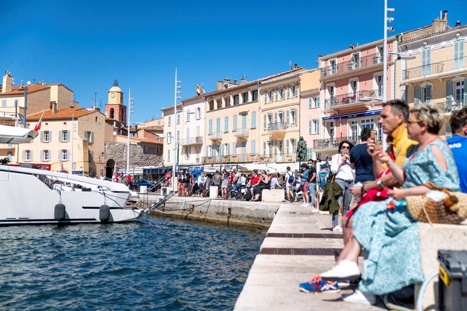 Menschen sitzen am Hafen von Saint Tropez: Wegen sinkender Corona-Infektionszahlen streicht die Bundesregierung am Sonntag auch fast ganz Frankreichvon der Liste der Risikogebiete.