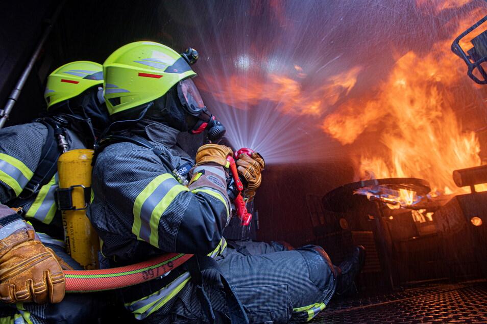 Einsatz im Brandübungscontainer: Felix Dehn und Sandro Funke von der Ortsfeuerwehr Uhyst testen hier das Löschen von brennenden technischen Geräten und spielen weitere Einsatzszenarien durch.