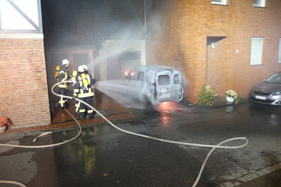 Feuerwehrleute löschen ein brennendes E-Auto, das während des Ladevorgangs in Flammen aufgegangen ist.