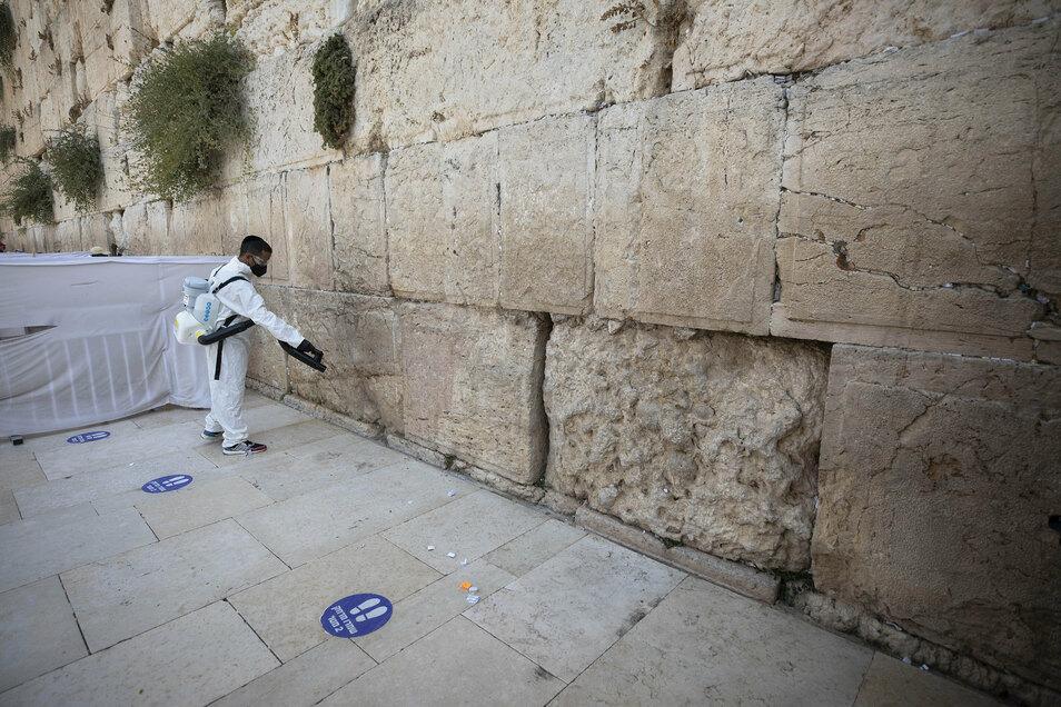 Ein Arbeiter verteilt Desinfektionsmittel als Vorsichtsmaßnahme gegen das Coronavirus an der Klagemauer, der heiligsten Stätte, an der Juden in Jerusalem beten können.