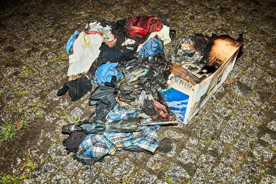 Die Überreste des angezündeten Kartons mit Kleidung.