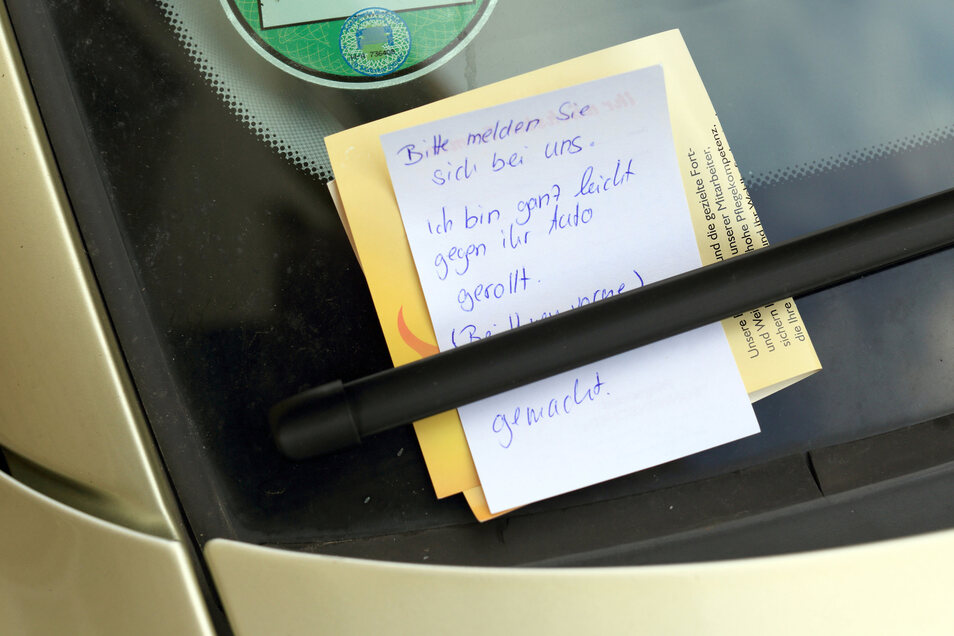 """Ein Zettel mit der Aufschrift: """"Bitte melden Sie sich bei uns. Ich bin ganz leicht gegen ihr Auto gerollt"""", klemmt an einem Auto.,"""