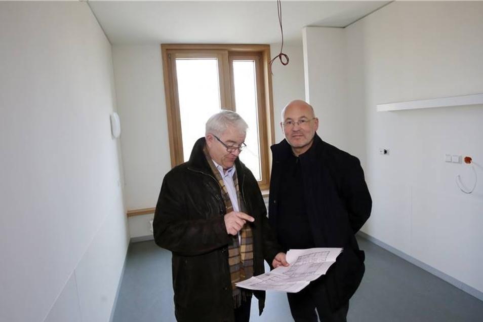 Lutz-Peter Petzold und Verwaltungsdirektor Matthias Grimm (re.) schauen sich in einem fast fertiggestellten Patientenzimmer die Baupläne an.