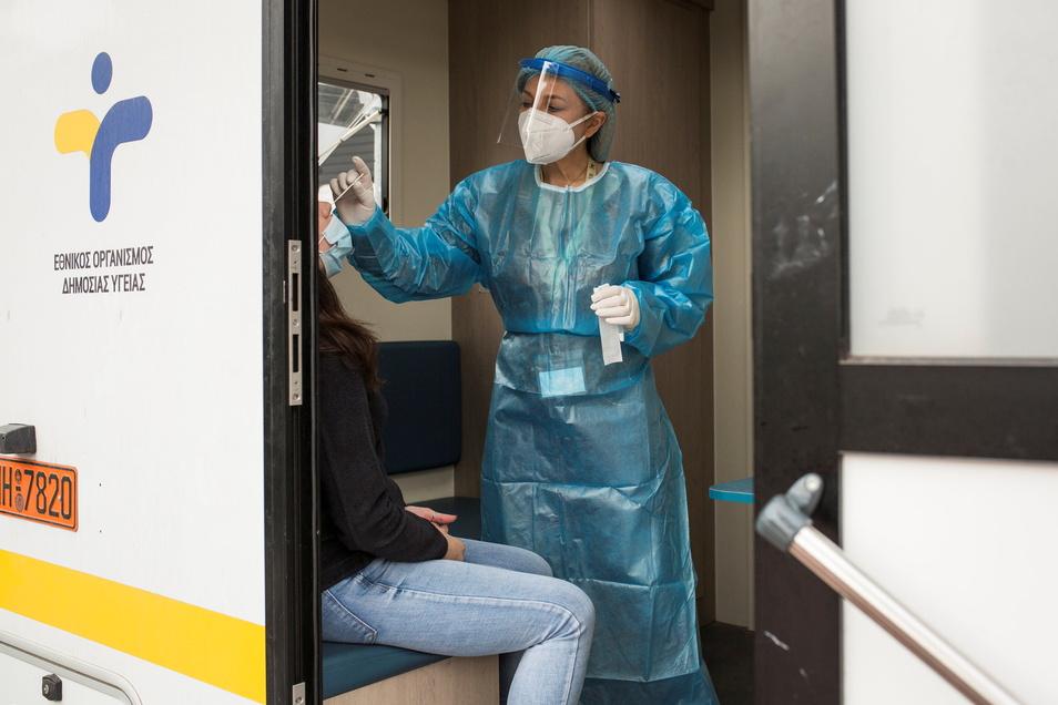 Eine Mitarbeiterin des Gesundheitswesens nimmt an einer Teststelle in Athen einen Abstrich vor.