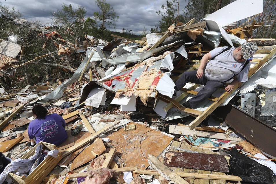 Menschen durchsuchen den zerstörten Wohnwagen in einem Wohnwagenpark.