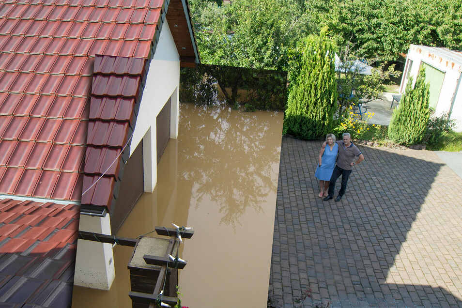 Die Foto-Montage zeigt Andrea und Dirk Haufe (rechts) heute auf dem trockenen Garagenvorplatz. Links ist der Wasserstand von vor zehn Jahren einen Tag nach dem Staudammbruch zu sehen, aufgenommen jeweils aus dem Badfenster des Hauses.