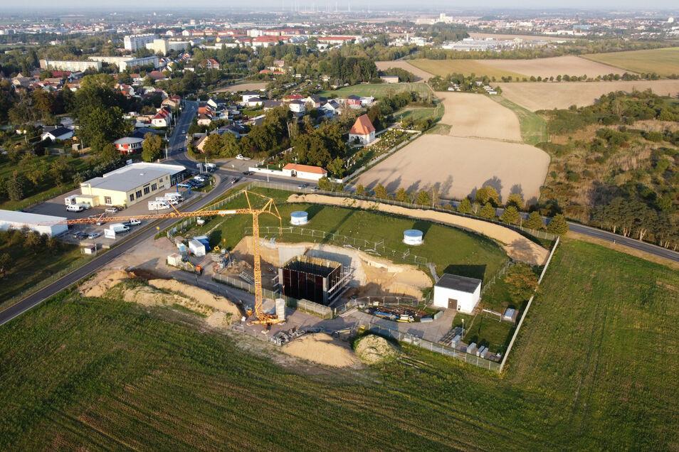 Ein Blick aus der Luft auf die höchste Baustelle Riesas: In der Baugrube entsteht ein neues Bediengebäude für die beiden Wasserspeicher unter dem künstlichen Hügel. Im Hintergrund: der Heidebergfriedhof, Weida und ganz hinten Riesas Innenstadt.