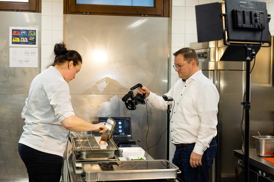 Köchin Margit Dippmann wird von Dehoga-Geschäftsführer Axel Klein gefilmt. Bei einem digitalen Kochworkshop der Dehoga lernen die Kochlehrlinge, was sie sonst im Berufsalltag ausprobieren könnten.