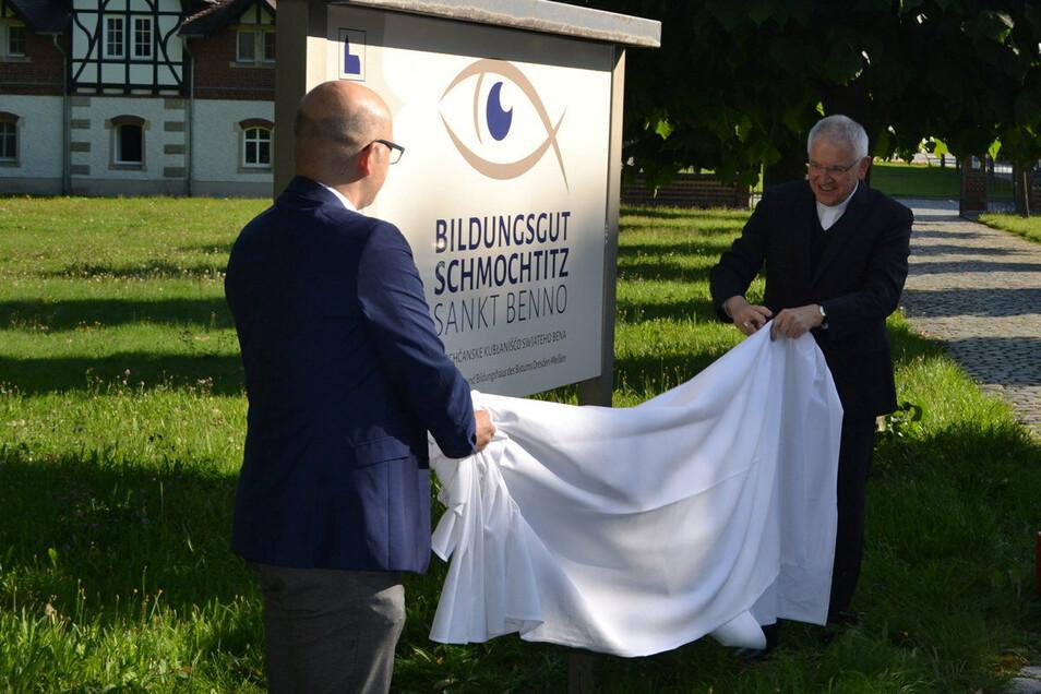 Vor dem neuen Bildungsgut in Schmochtitz enthüllen Rektor Sebastian Kieslich (l.) und Bischof Heinrich Timmerevers die Tafel mit dem Namen.