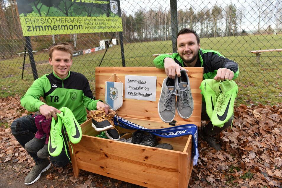 In dieser Kiste am Sportplatz in Seifersdorf wollen Toni Richter (links) und Daniel Pschorn vom TSV Seifersdorf Schuhe sammeln und damit die Vereinskasse aufbessern.