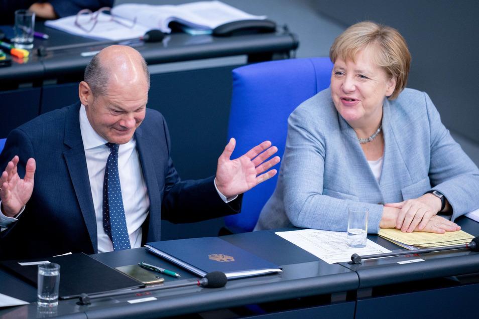 Bundeskanzlerin Angela Merkel (CDU, r) und Olaf Scholz (SPD), Bundesminister der Finanzen, unterhalten sich am Dienstag im Bundestag Bundestag zu Beginn der Haushaltswoche.