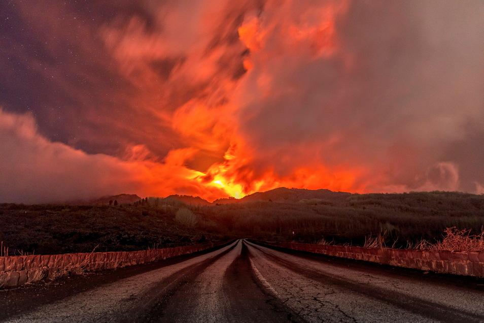 Ein glühender Lavastrom fließt über den Ätna, der von Rauch umgeben und über dem ein rötlich gefärbter Himmel zu sehen ist.