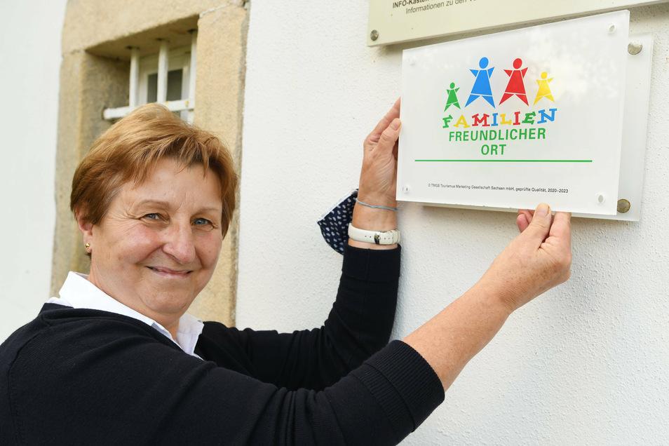 """Renate Lösel, Mitarbeiterin in der Jonsdorfer Touristinformation, kann das neue Gütesiegel am Haus anbringen. Seit Jahren erfüllt die Gemeinde alle Kriterien für das Zertifikat """"Familienfreundlicher Ort""""."""
