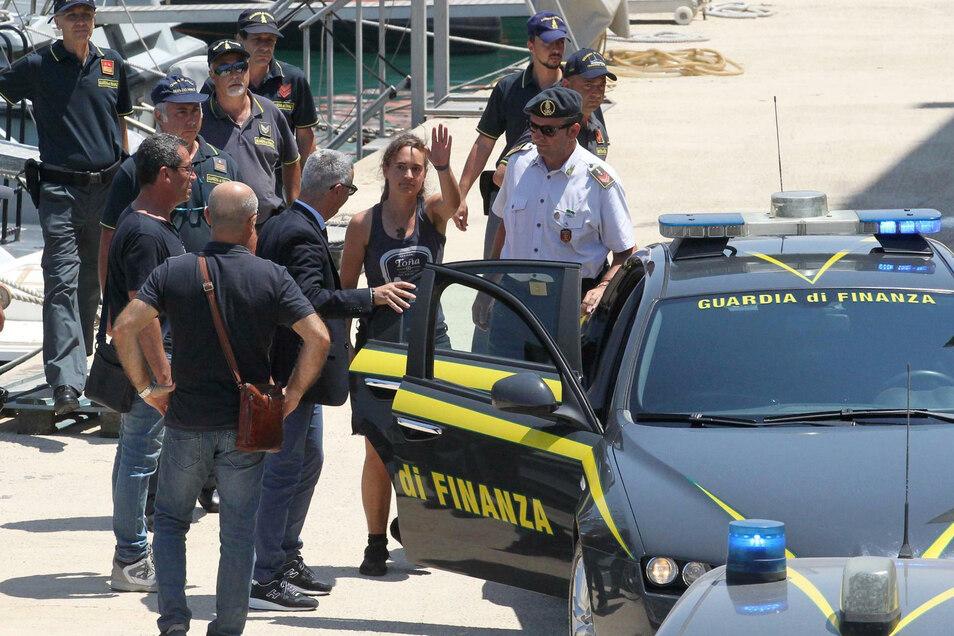 Carola Rackete (M), deutsche Kapitänin der Sea-Watch 3, steigt nach ihrer Ankunft im Hafen von Porto Empedocle in ein Polizeiauto.