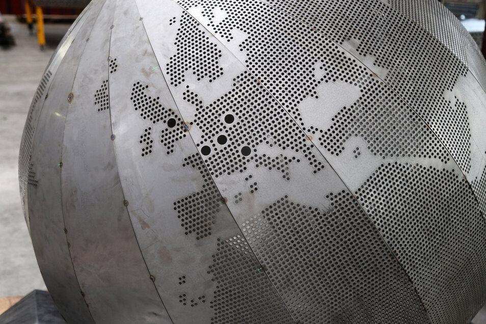 In der Weltkugel - getragen von drei Riesen -leuchten dann die Partnerstädte Riesas auf.