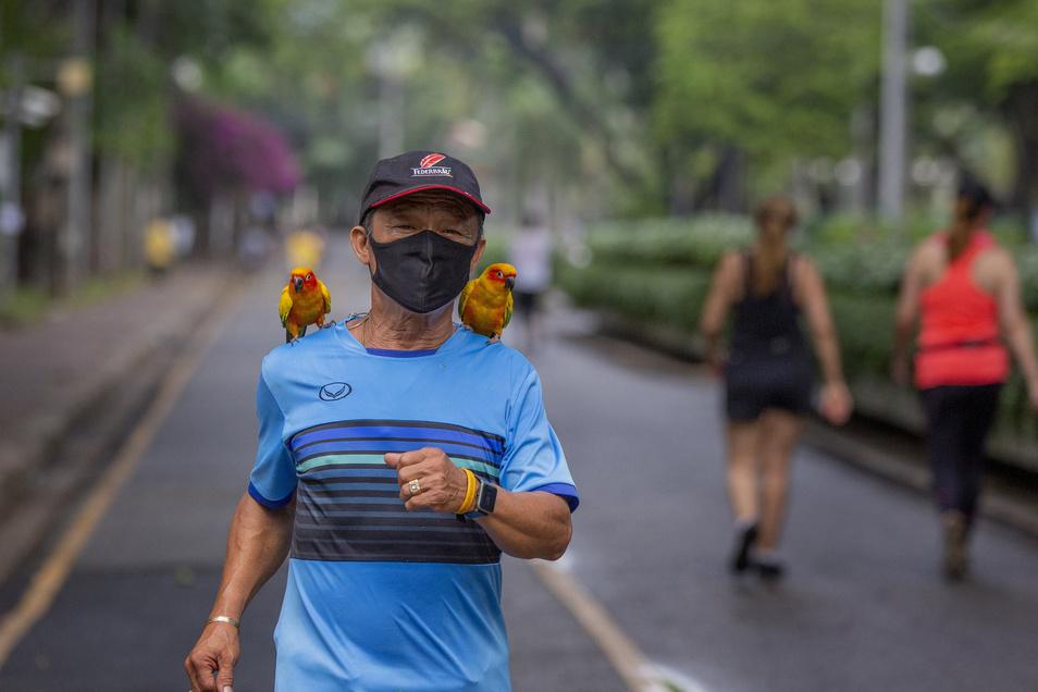 Ein Mann joggt mit seinen Hauspapageien auf den Schultern.