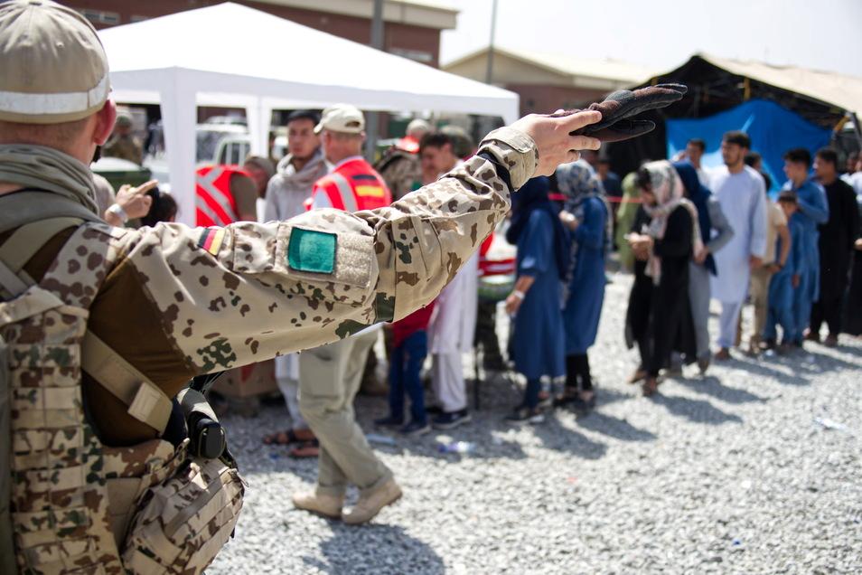 Kabul: Soldaten der Bundeswehr und Helfer verteilen eine Spende an Menschen, die auf eine Ausreisemöglichkeit warten.