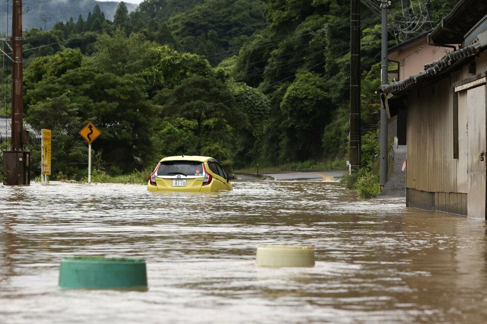 Ein Auto steckt auf einer durch starken Regen überschwemmten Straße in Yatsushiro fest.