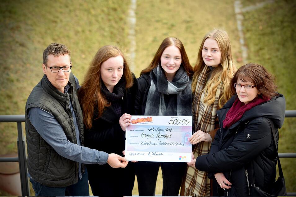 Einen Scheck über 500 Euro haben Marlene, Sarah und Vanessa (v. l.) und Lehrerin Heike Poitschke an den Herrnhuter Hospiz-Leiter Rene Rixrath übergeben.