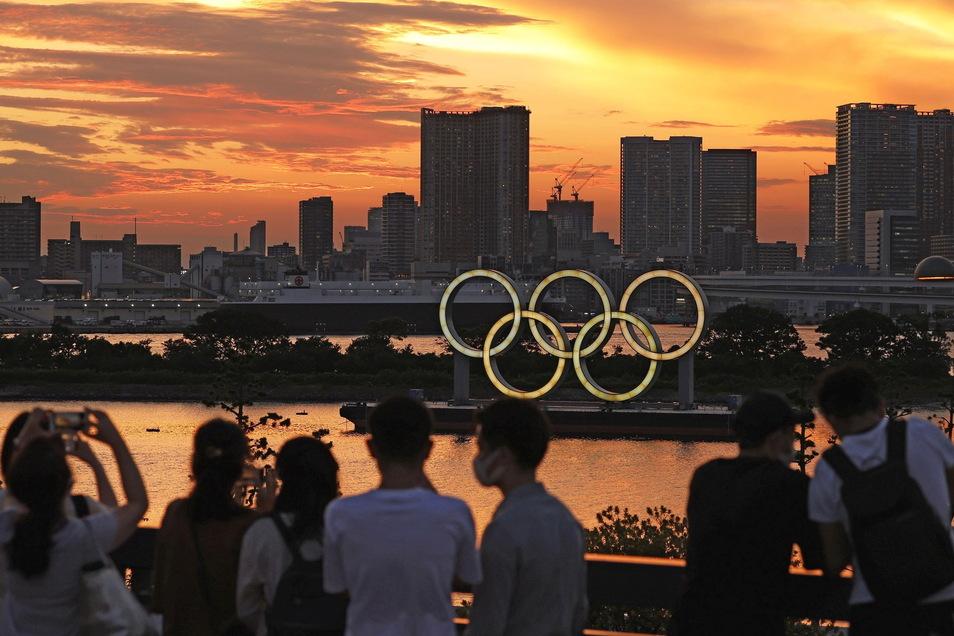 Menschen schauen auf die bei Sonnenuntergang beleuchteten olympischen Ringe in der Bucht von Tokio.