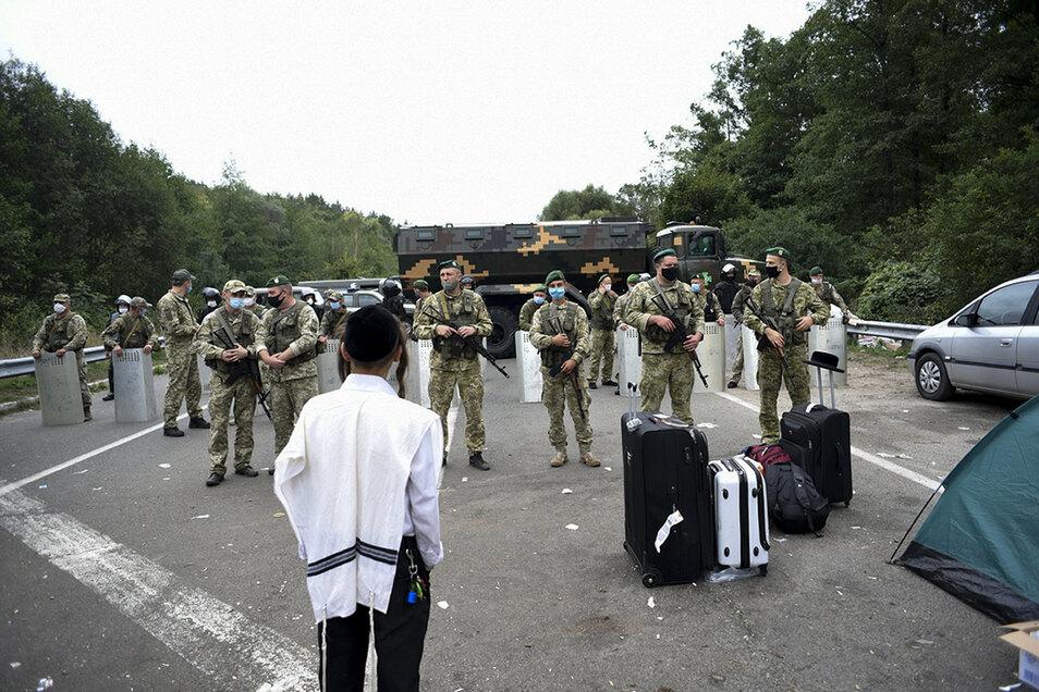 Ukrainische Grenzsoldaten blockieren die Straße an der ukrainisch-belarussischen Grenze. Mehrere Hundert ultraorthodoxe jüdische Pilger sitzen wegen eines Einreisestopps für Ausländer an der Grenze fest.