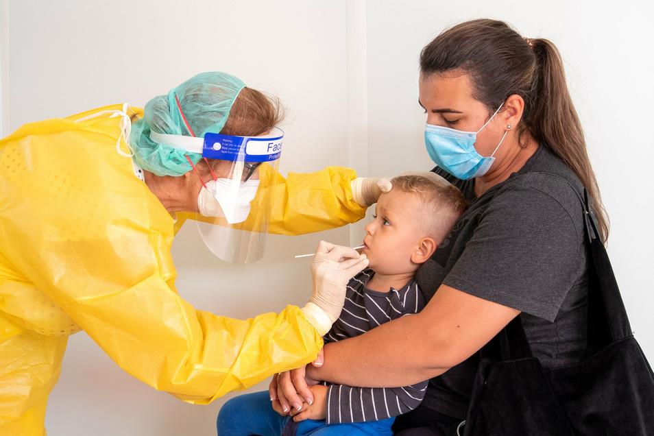 Mund auf, Stäbchen rein: Auch wenn der zweijährige Amar von Mutter Fatime gehalten wird, wäre er jetzt lieber ganz woanders, als im Corona-Testcontainer von Ärztin Ildiko Hollós an der Autobahn 17.