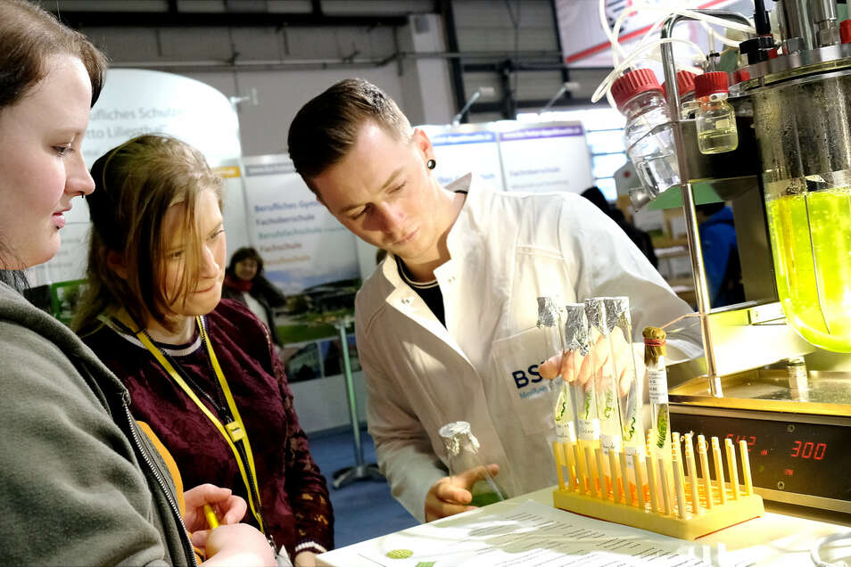 Nadine Rülcken und Christin Schanz aus Dresden lassen sich von Till Biebach vom BSZ Radebeul die Funktion eines Bioreaktors mit einer Algenlösung erklären.