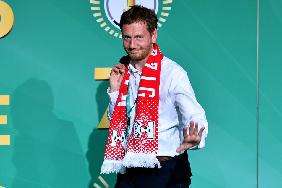 Sachsens Ministerpräsident Michael Kretschmer (CDU), hier beim DFB-Pokal-Endspiel im Vorjahr mit Schal das damaligen Finalisten RB Leipzig, spricht sich für die Fortsetzung der Bundesliga-Saison aus.